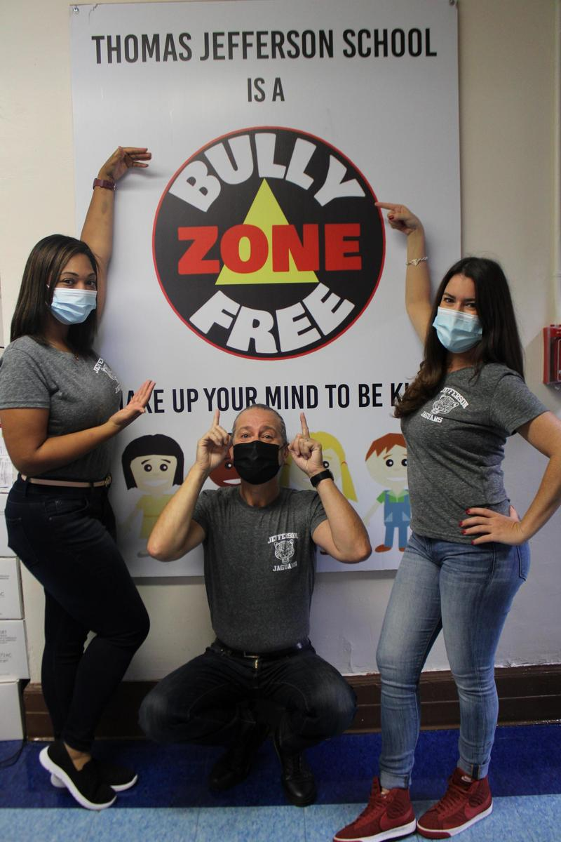 3 teachers posing with bully free zone poster