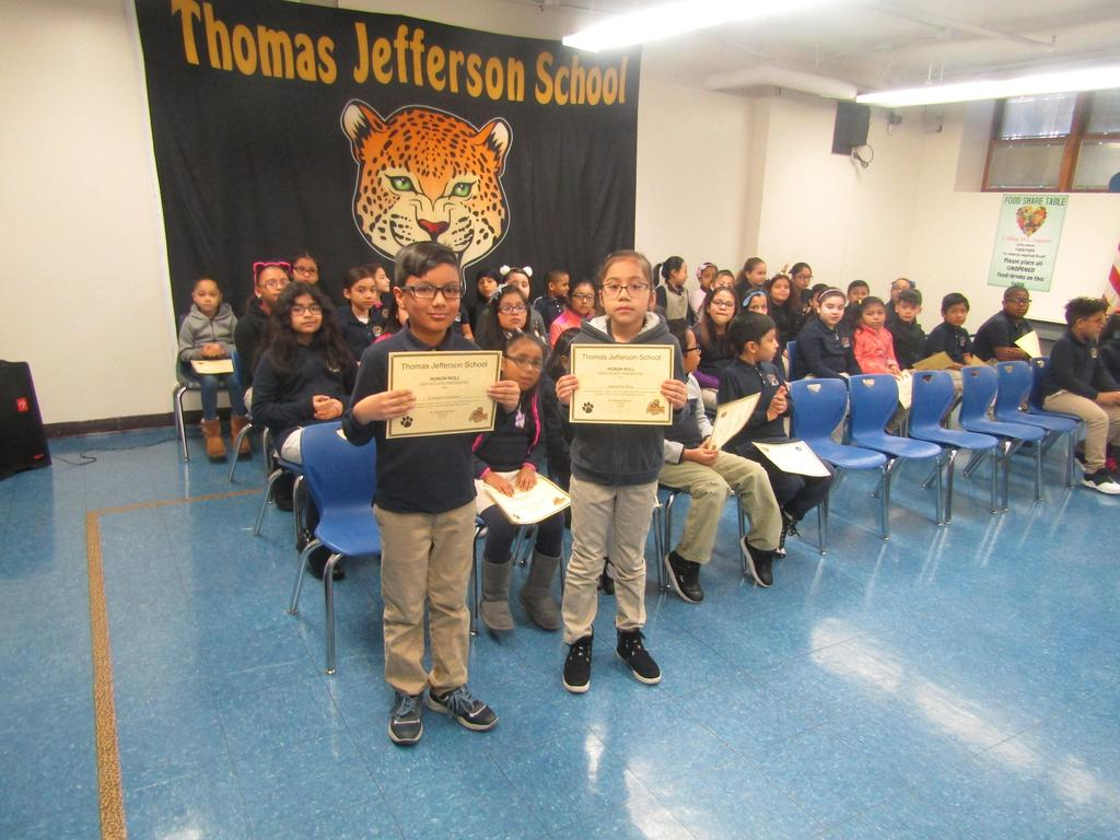 two kids holding up their honor roll certificates