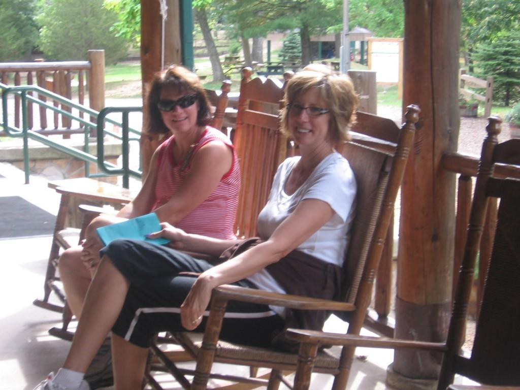 chaperones in rocking chairs on cabin porch