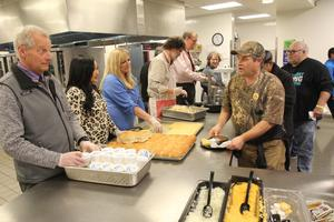 administrators serving food to a line of people