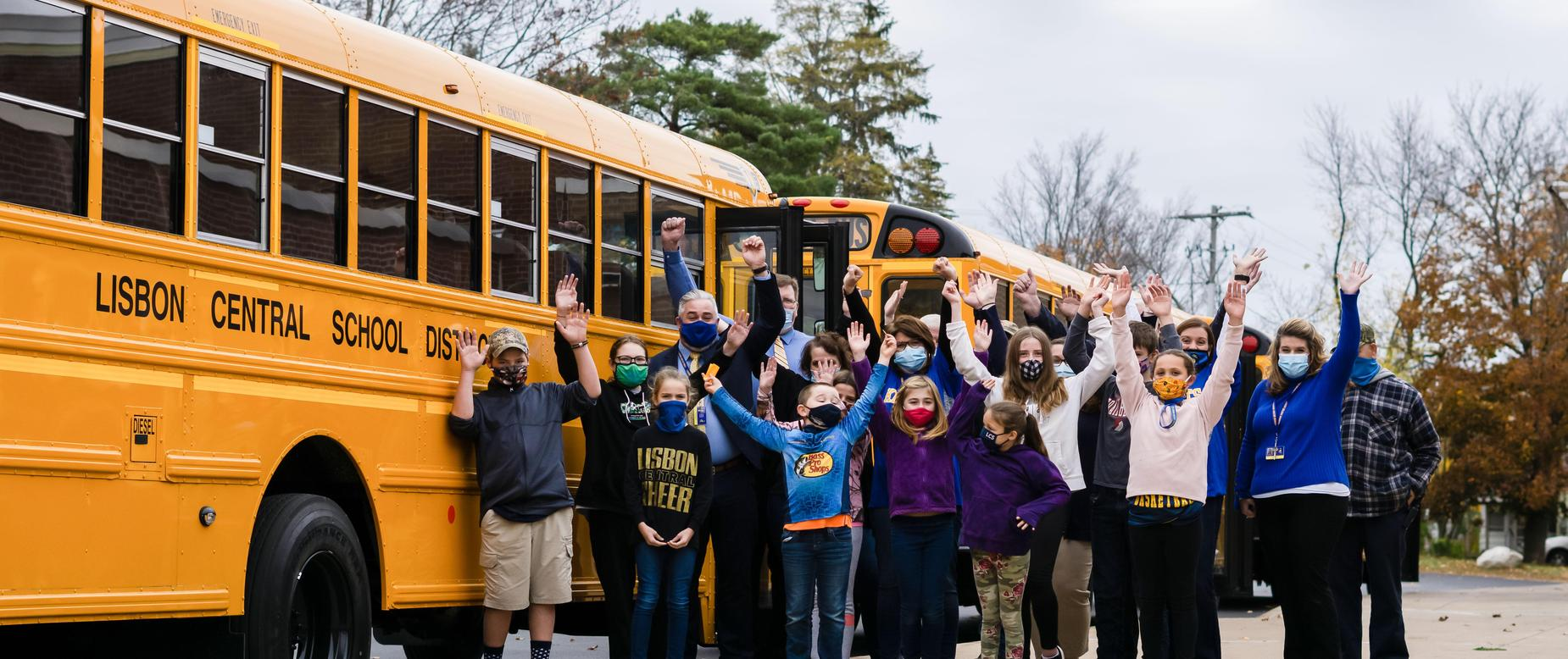 students and staff in front of the new school buses