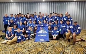 BHS Robotics Team poses with their banner at the Robotics World Championships in Detroit. They are wearing their Bensalem blue t-shirts.