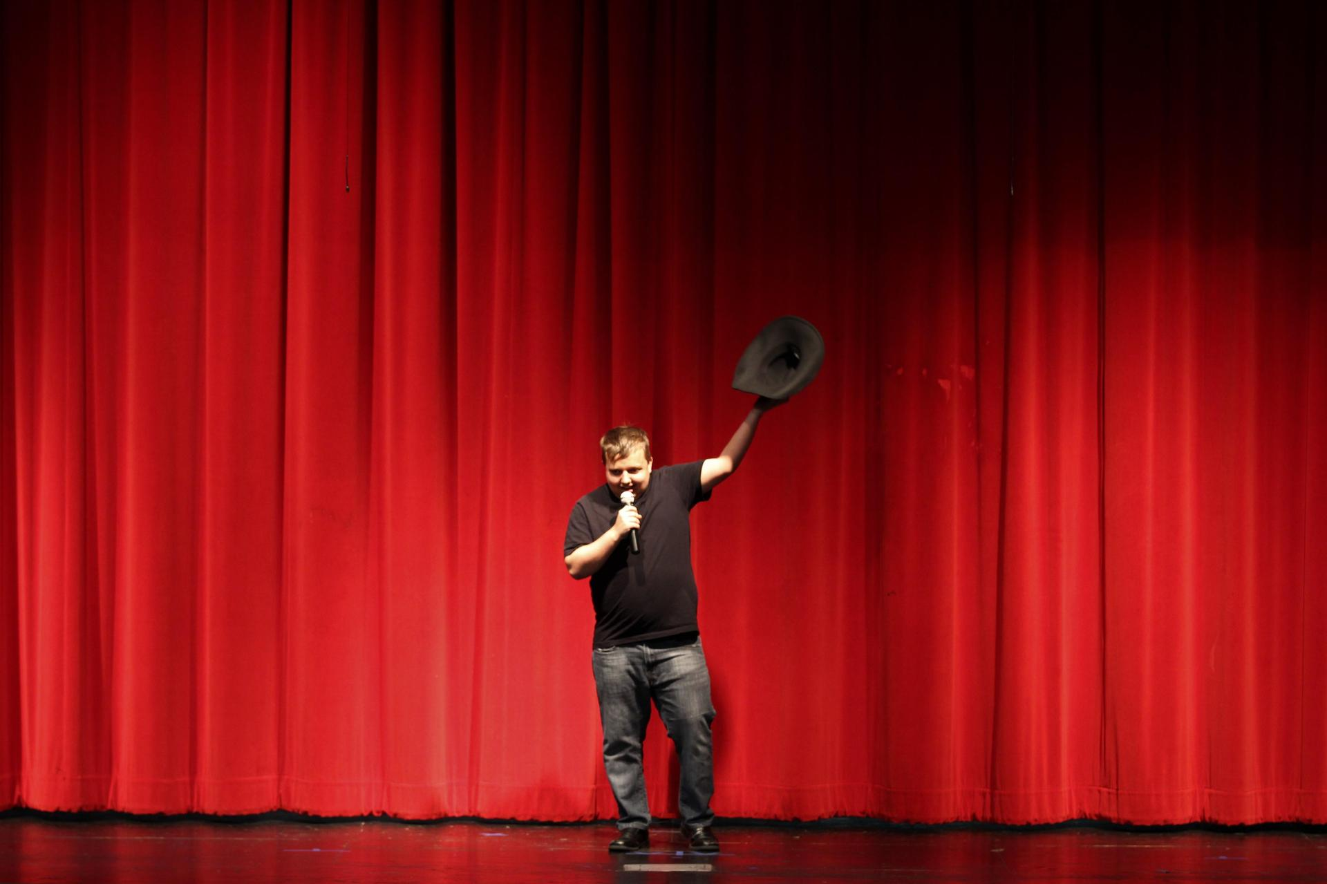 Jaxon Powell raising his hat in the air and singing at the Talent Show