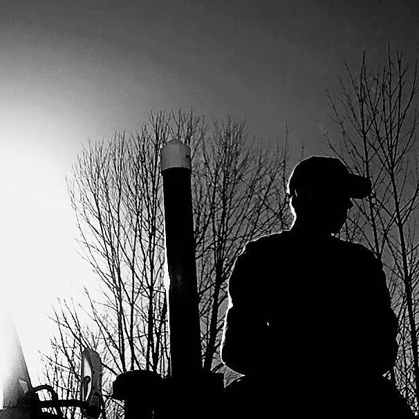 Silhouette of a students sitting on a tractor with the setting sun behind him.
