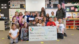 Teacher Quincey Williamson and Principal Steve LaBau pose with students and a check from the Nampa Schools Foundation.
