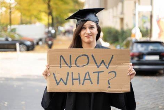 graduate with a sign that reads now what?