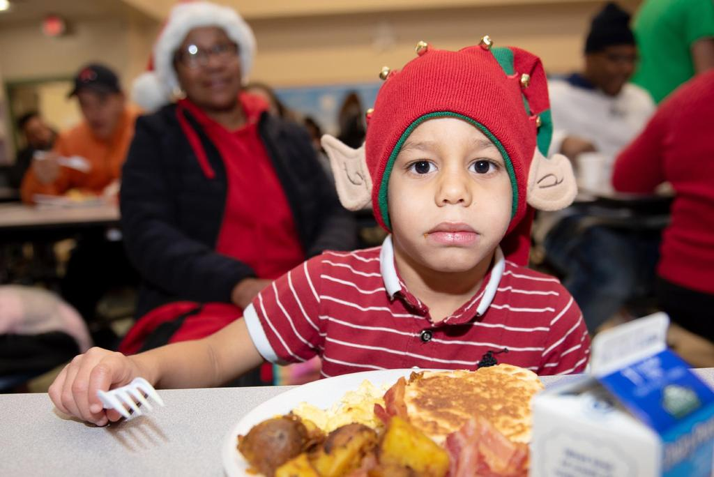 A student wearing an elf hat seated in front of a full breakfast
