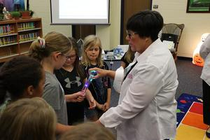 One of the Consumers Energy representatives shows a student how the energy baton works.