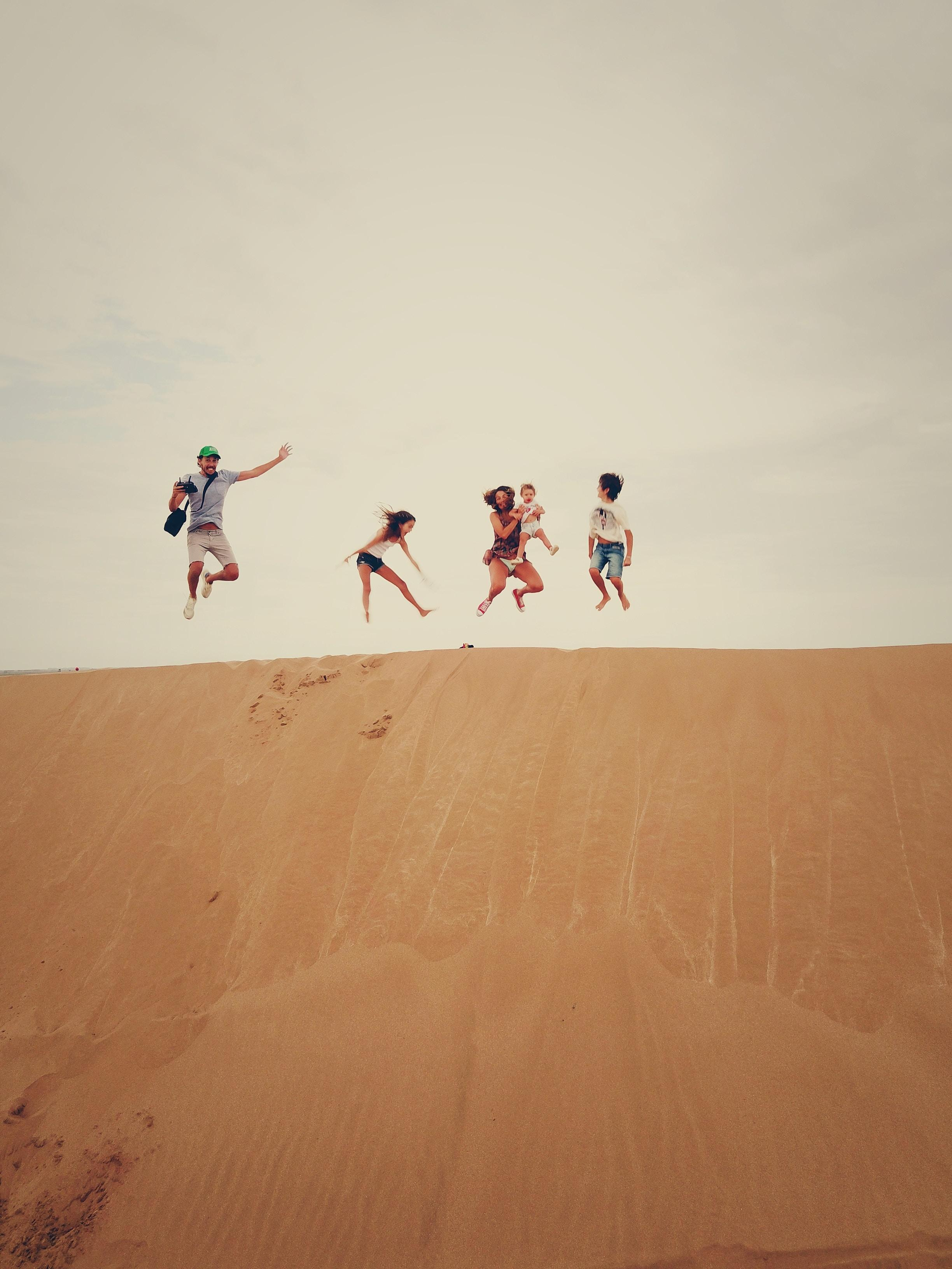 A family jumping into the air over a sand dune