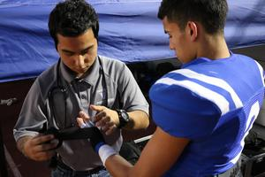 Alexis Aranda shown taping the wrist of a football player