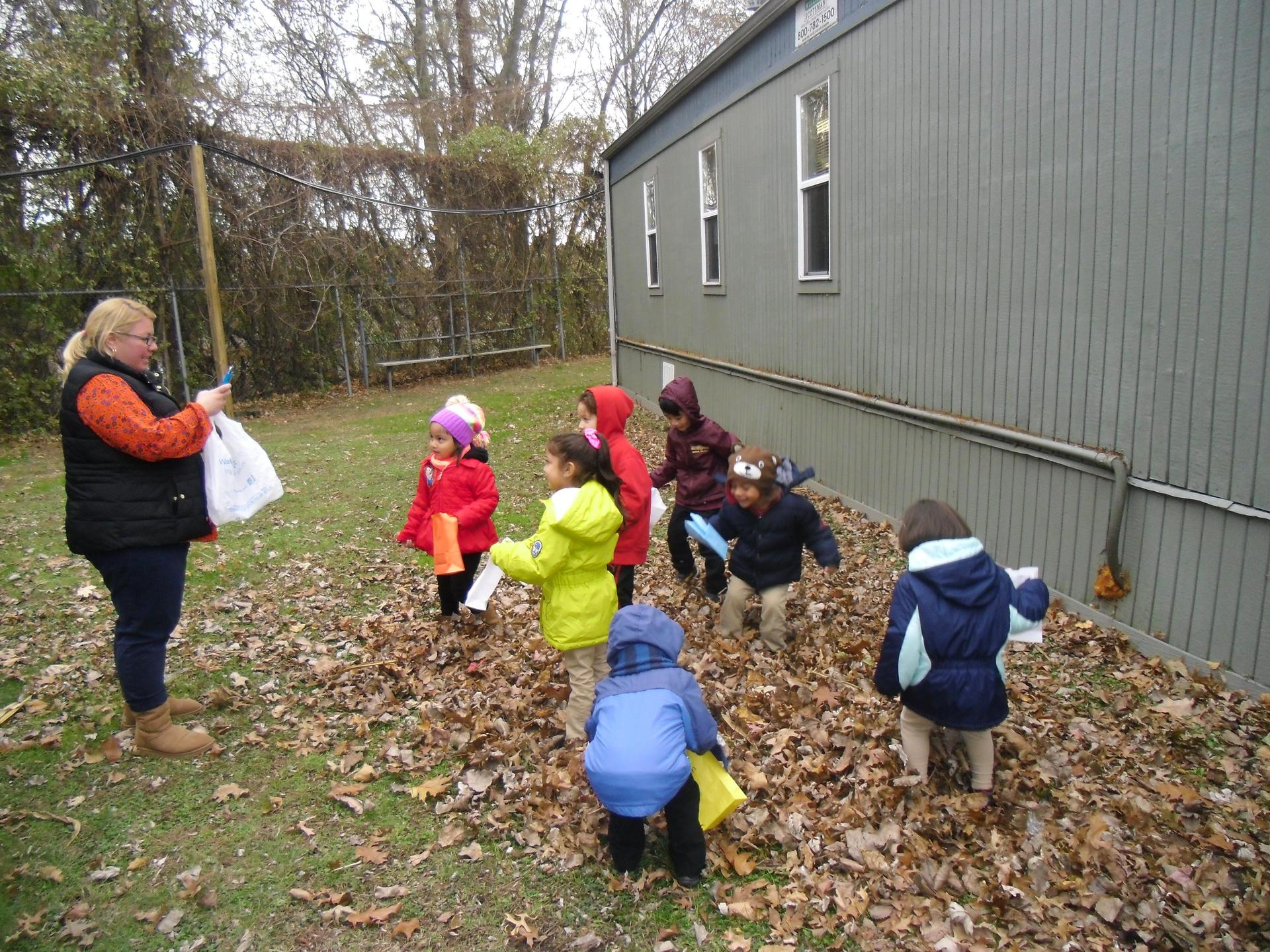 North Bergen Students experiencing nature by touching and seeing leaves with their teacher.