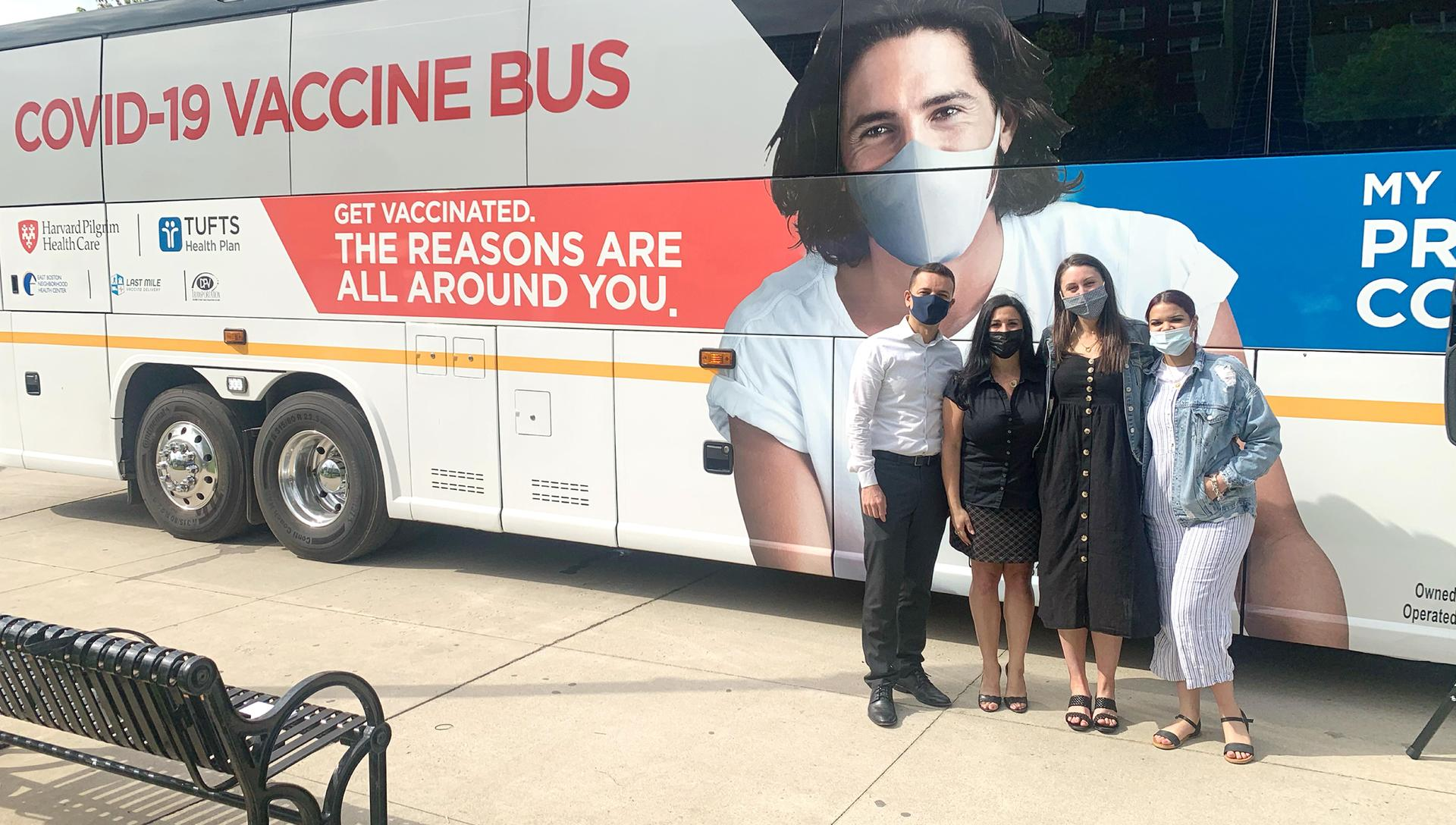 Adults standing in front of a mobile vaccine clinic