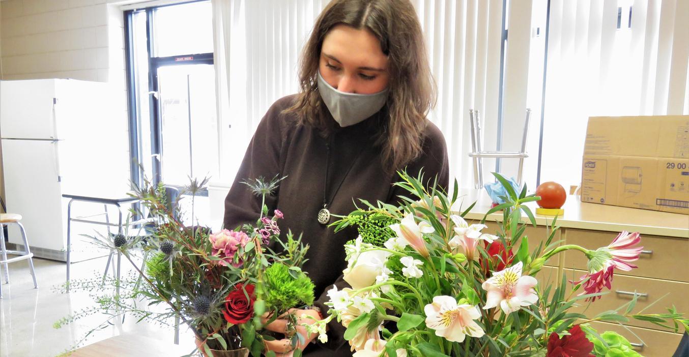 A TKHS student works on a flower arrangement.