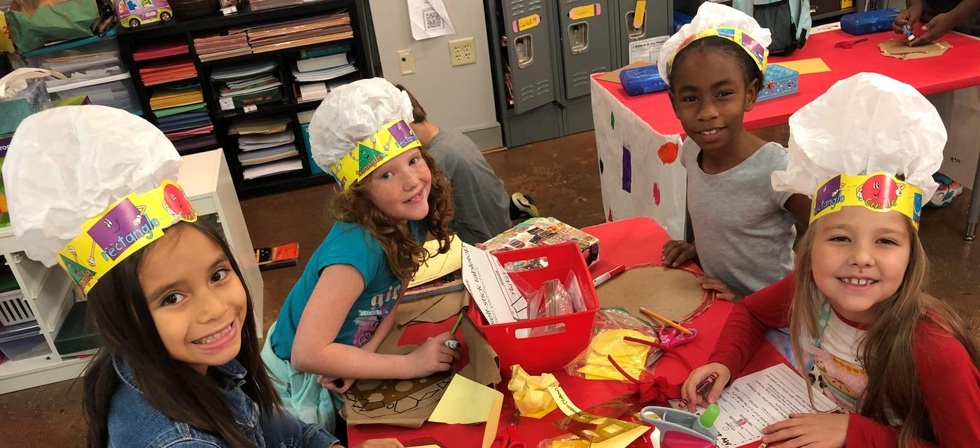 four girls wearing chef hats learning while getting crafty