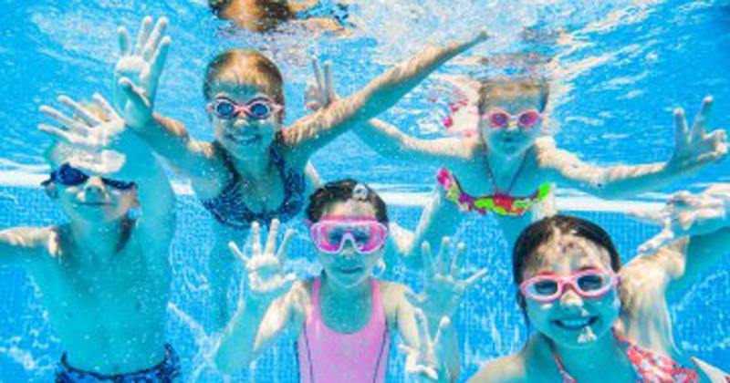 Children in pool during summertime.