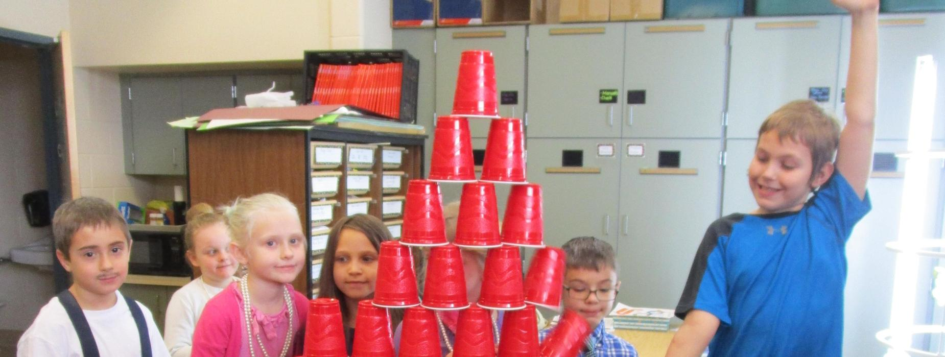 Several elementary students with a pyramid they build out of red solo cups thirteen rows high as part of the 100th day of school celebration.