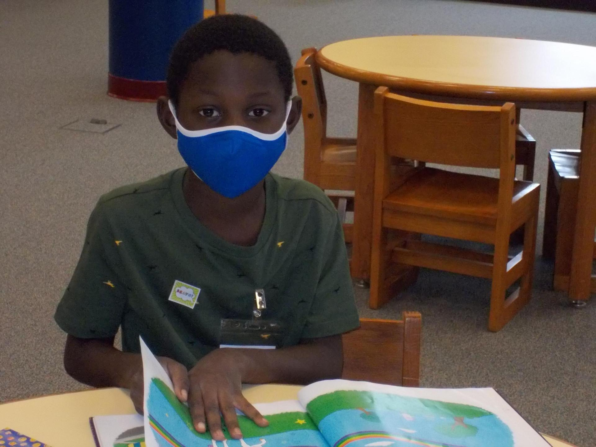 A student reads with his mask on