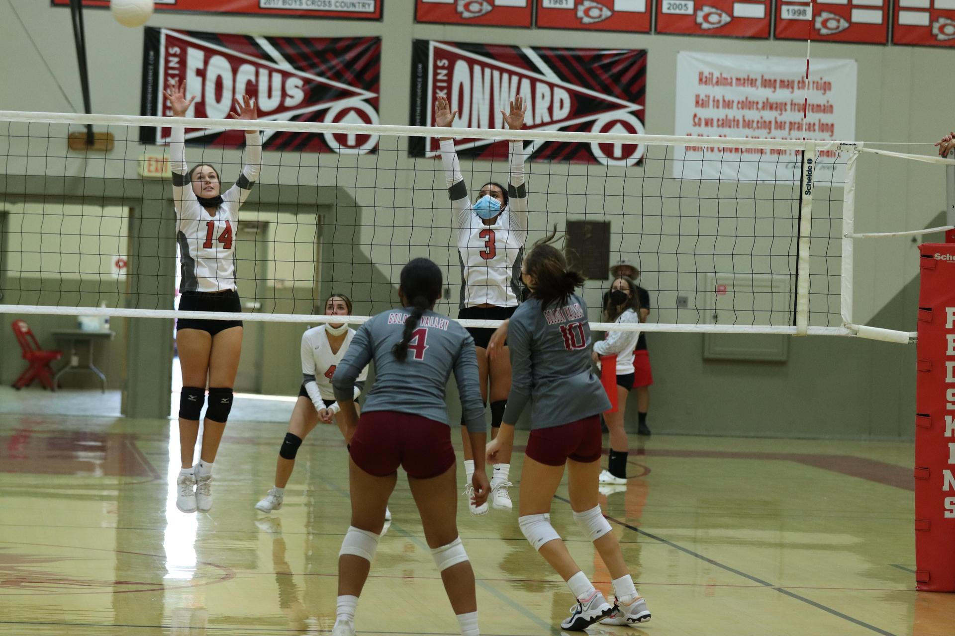 Varsity girls playing volleyball against Golden Valley