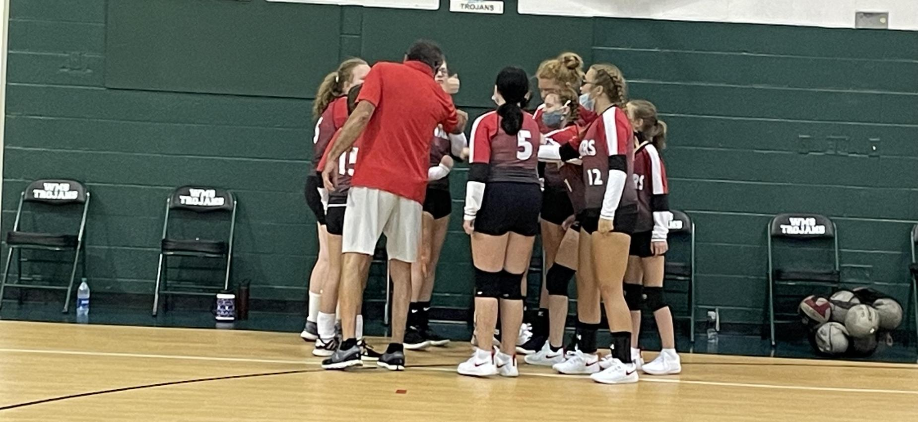 A group of volleyball players gathers with the coach.