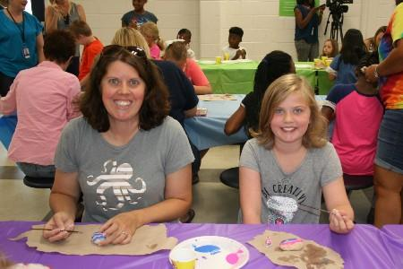 Parent and student painting rocks.