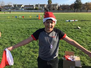 student standing in a race track field with a santa hat on and a santa hat in his hand