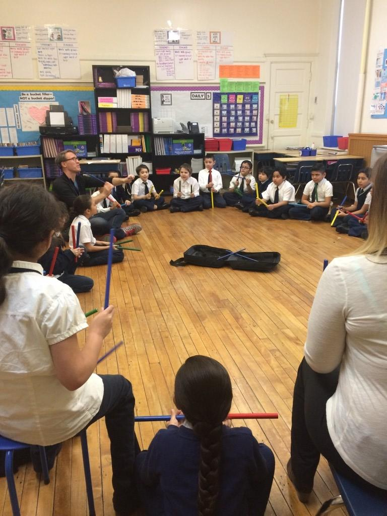 Mr. Matt teaching how to use drum sticks with our third grade Ravinia kiddos!
