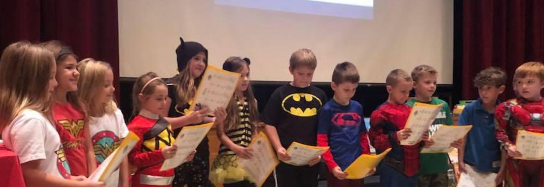 Students presenting on super heroes at an assembly