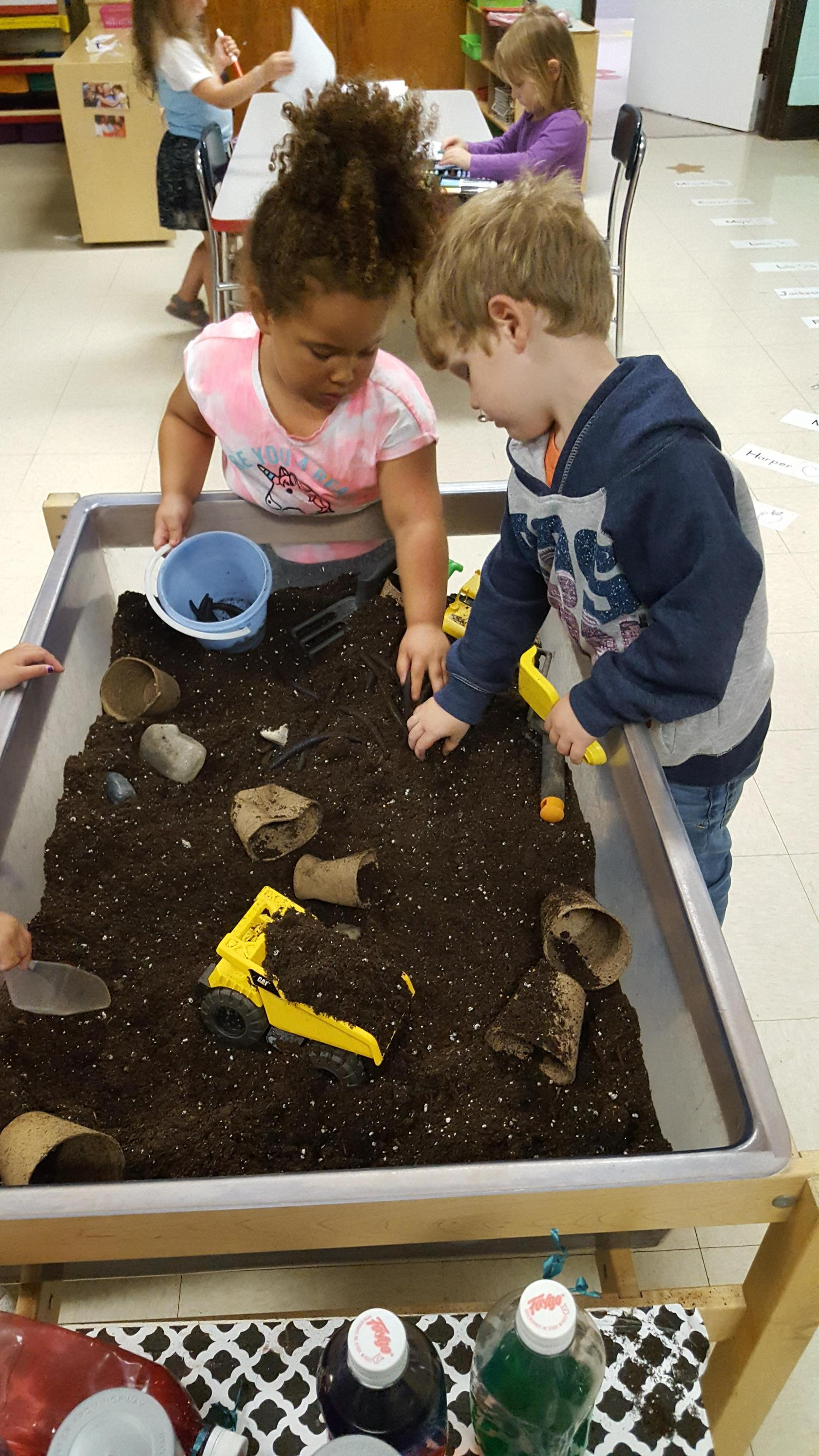 GSRP students playing in potting soil during  a gardening project.