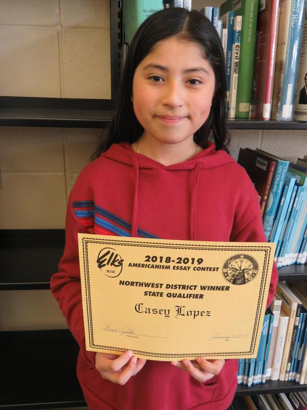 Casey Lopez receives an award for her essay.