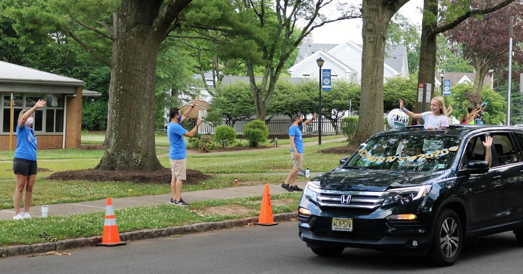 Photo of teachers and staff waving as 5th graders and families pass by during Grade 5 Clap Out Car Parade.