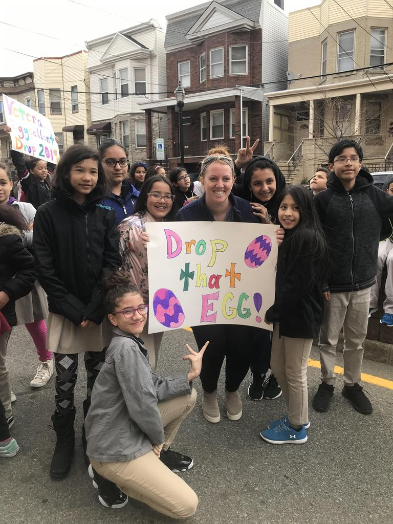 "A female teacher with her class holding sign ""Drop that Egg"""