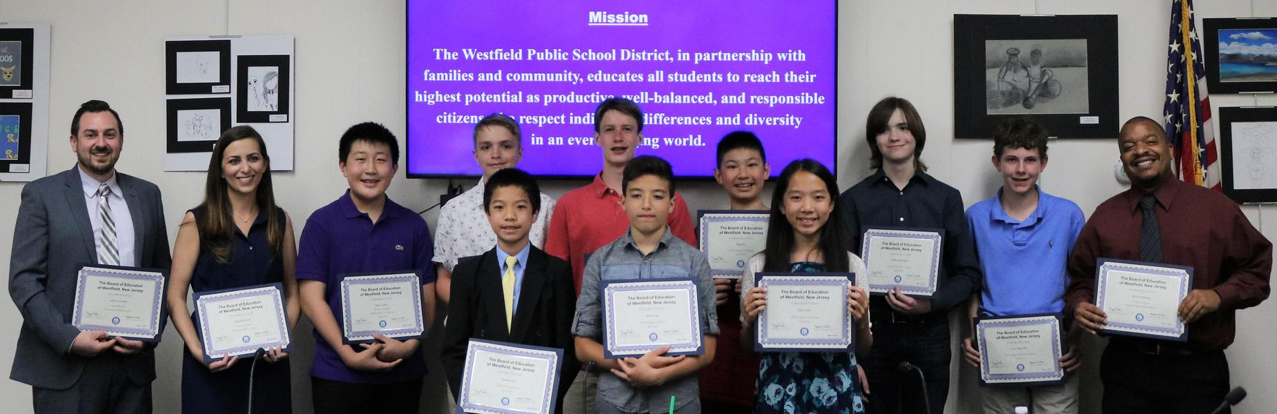 Photo of intermediate school student musicians and their instructors holding Certificates of Recognition at May 21 Board of Education meeting.
