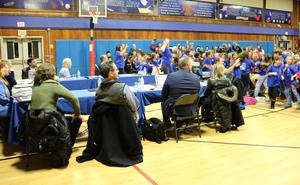 Photo of Board of Education members smiling as Washington School students and staff dance during a Blue Ribbon celebration.
