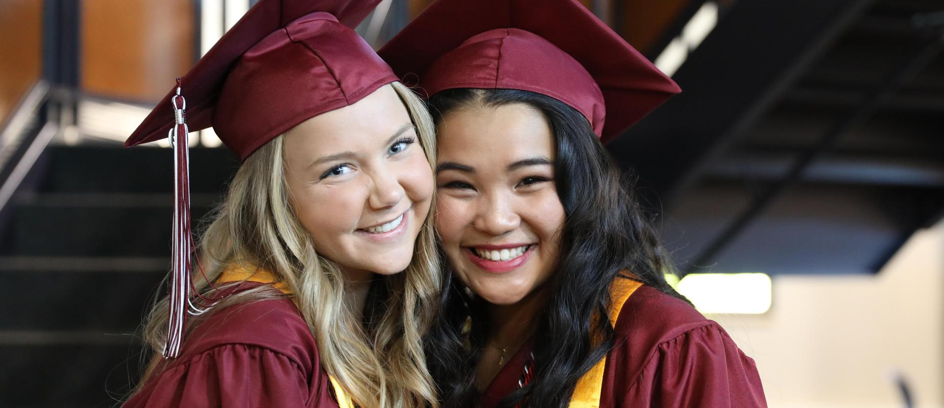two girls in maroon caps and gowns in hallway