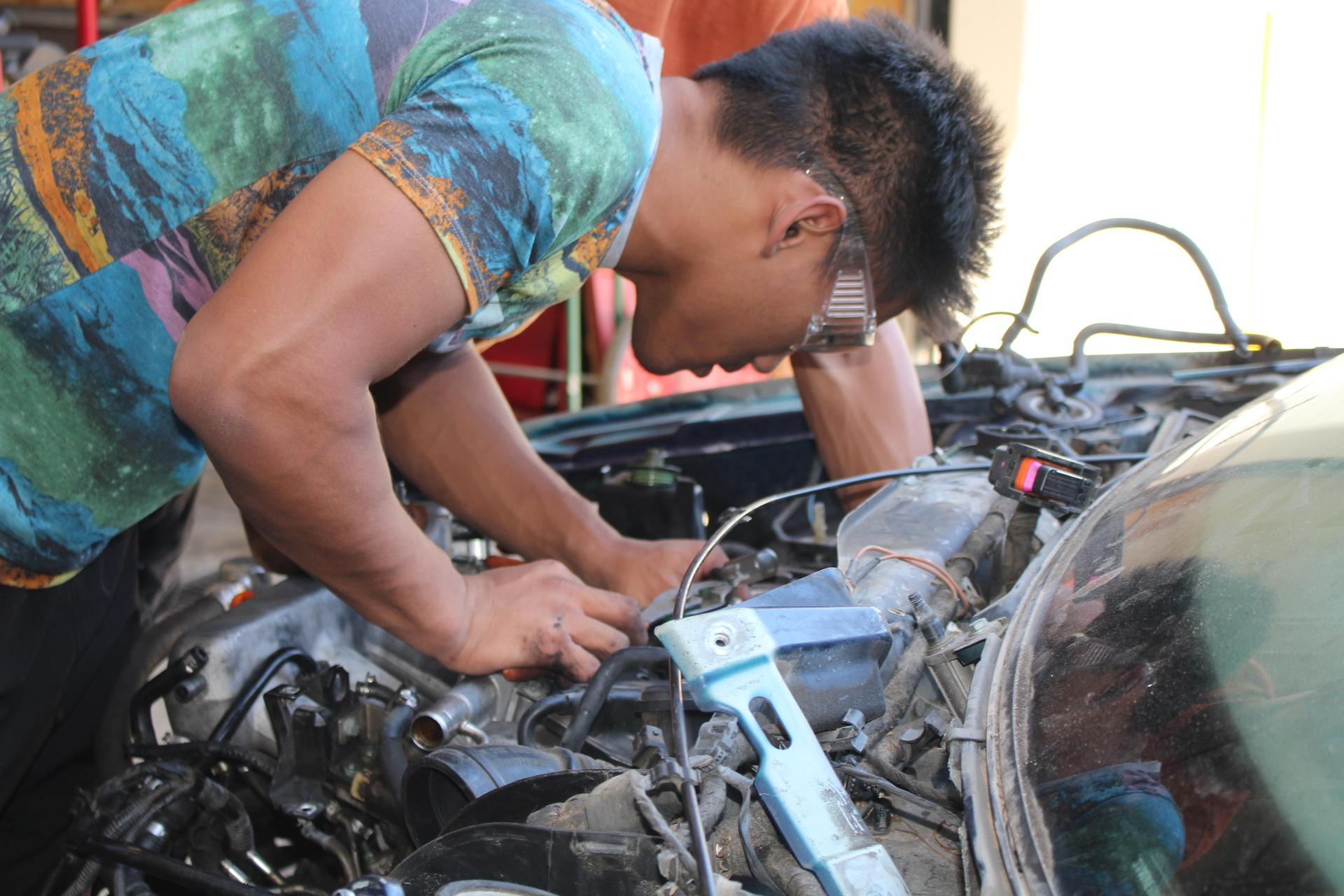 Male student checking out an engine