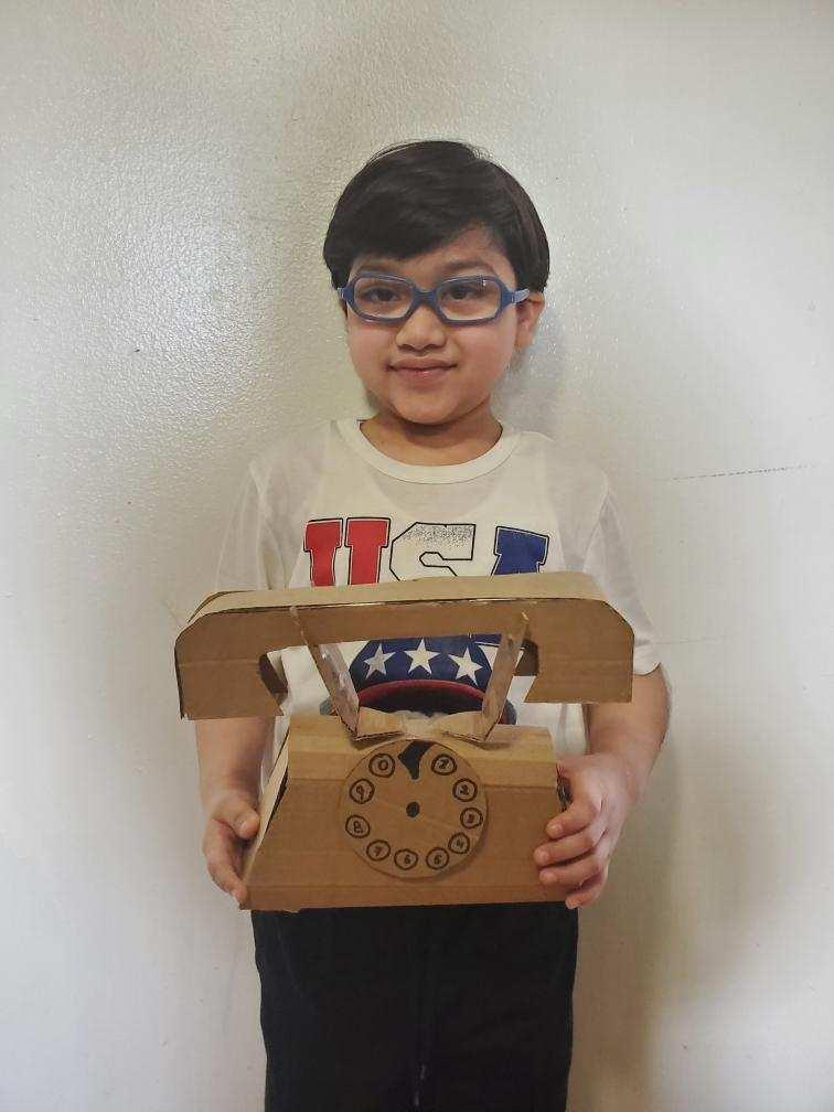 boy with glasses holding up a cardboard old rotary phone