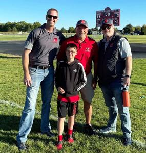 Shaun Roberts, in a red shirt, poses in front of the scoreboard with two school administrators and a young boy.
