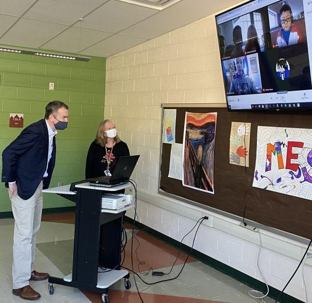 Virginia Governor Ralph Northam speaks virtually with members of Marion Elementary School's STEM Competition Team, as team sponsor and MES school counselor Kay Richardson looks on.