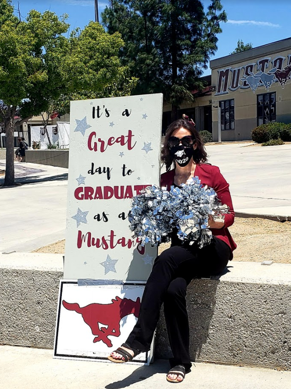 Jody Mendivil wearing a mask and sitting in front of a handmade West Valley sign.