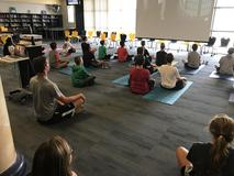 Coach East's class participating in a yoga session in the library!