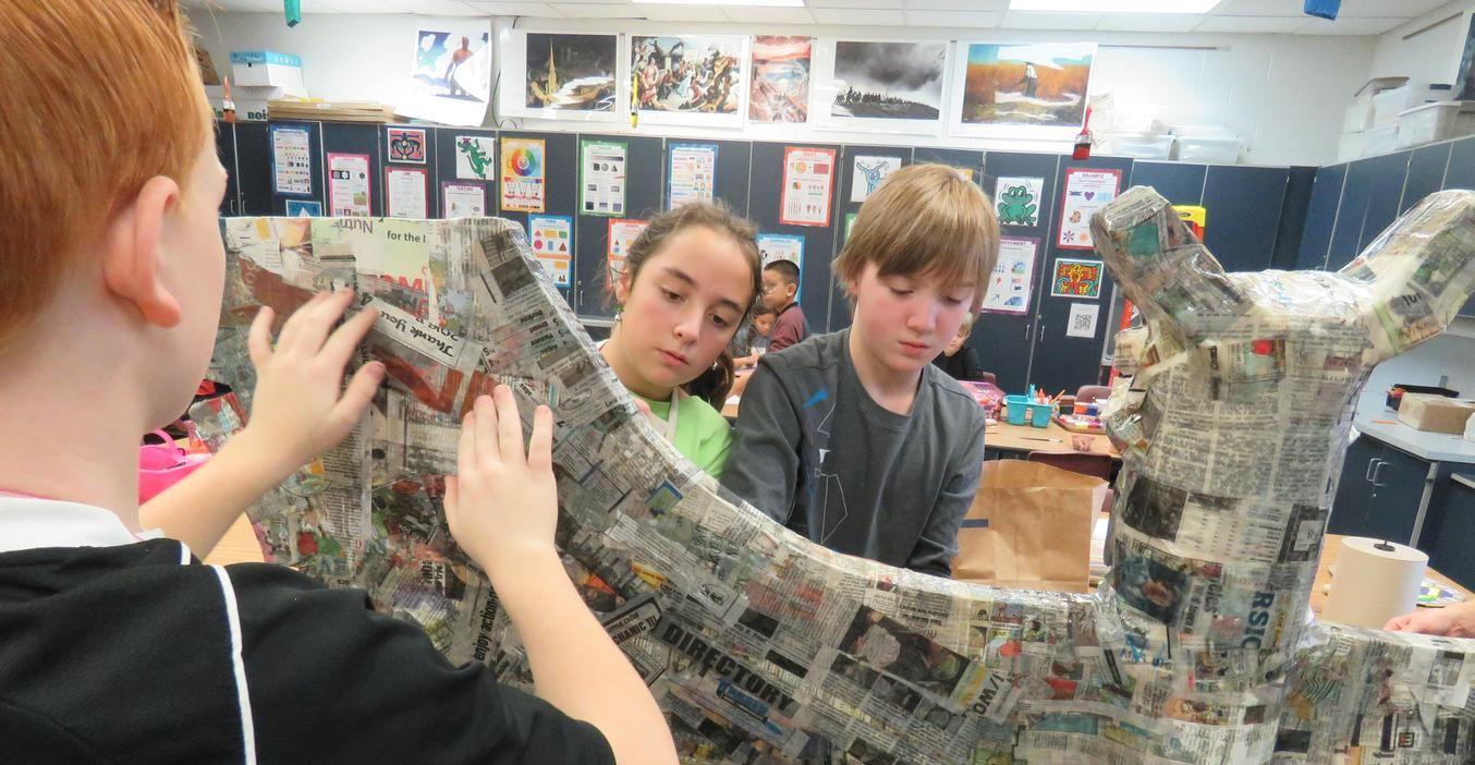 Page students work on a papier mache totem pole project.