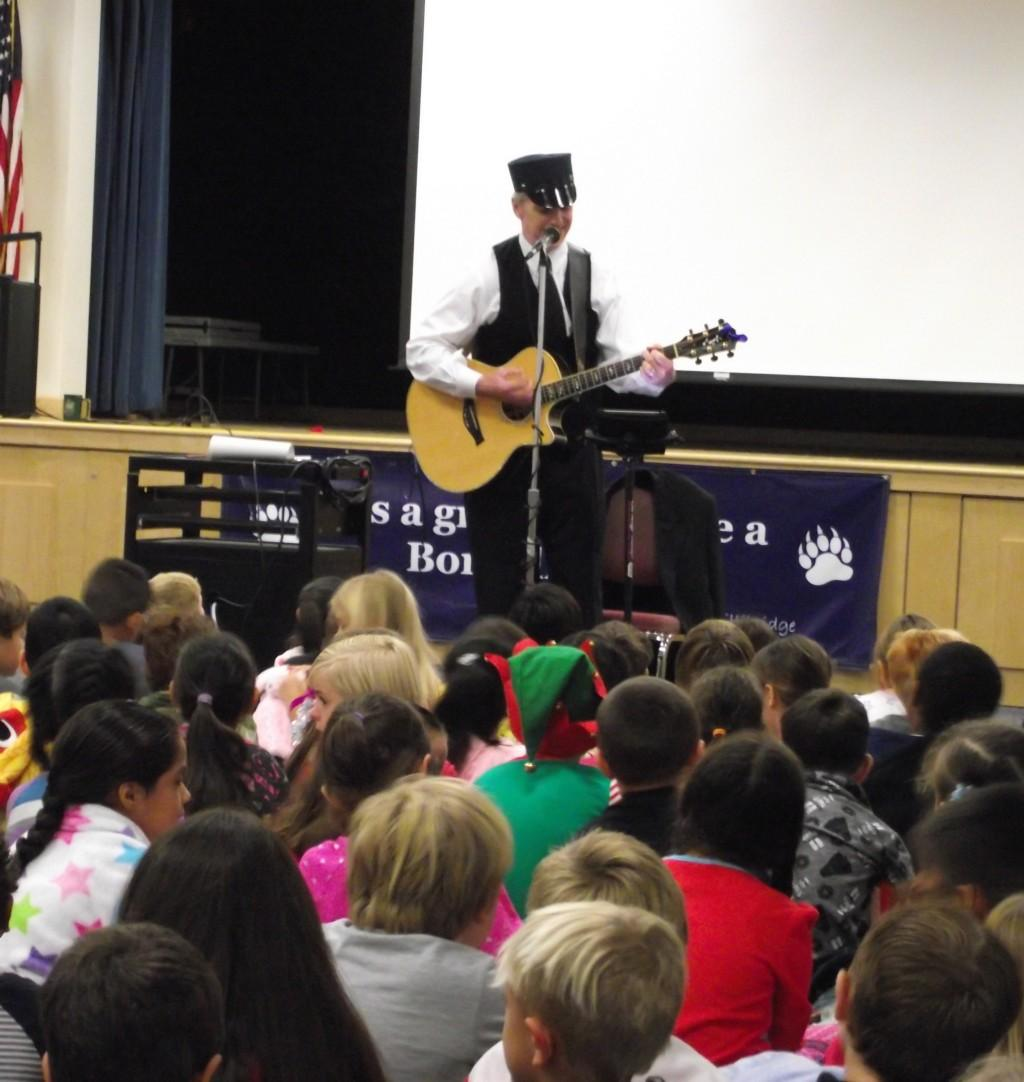 Dr. Justin Cunningham playing the guitar and singing to Bonsall first graders during their polar Express day