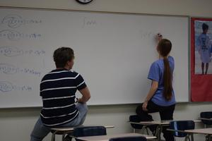 girl standing in front of white board in classroom