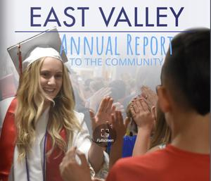 Cover of the Annual Report showing a blonde, female high school graduate giving high-5's to children at East Valley Elementary School.
