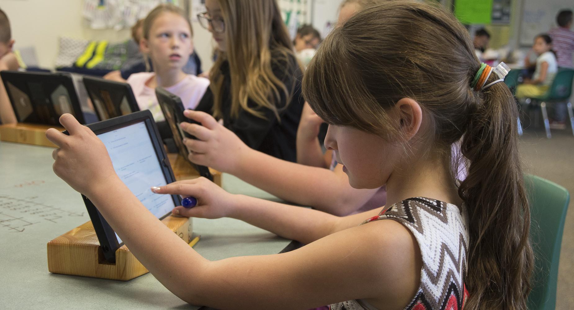 Girl at desk work on iPad.