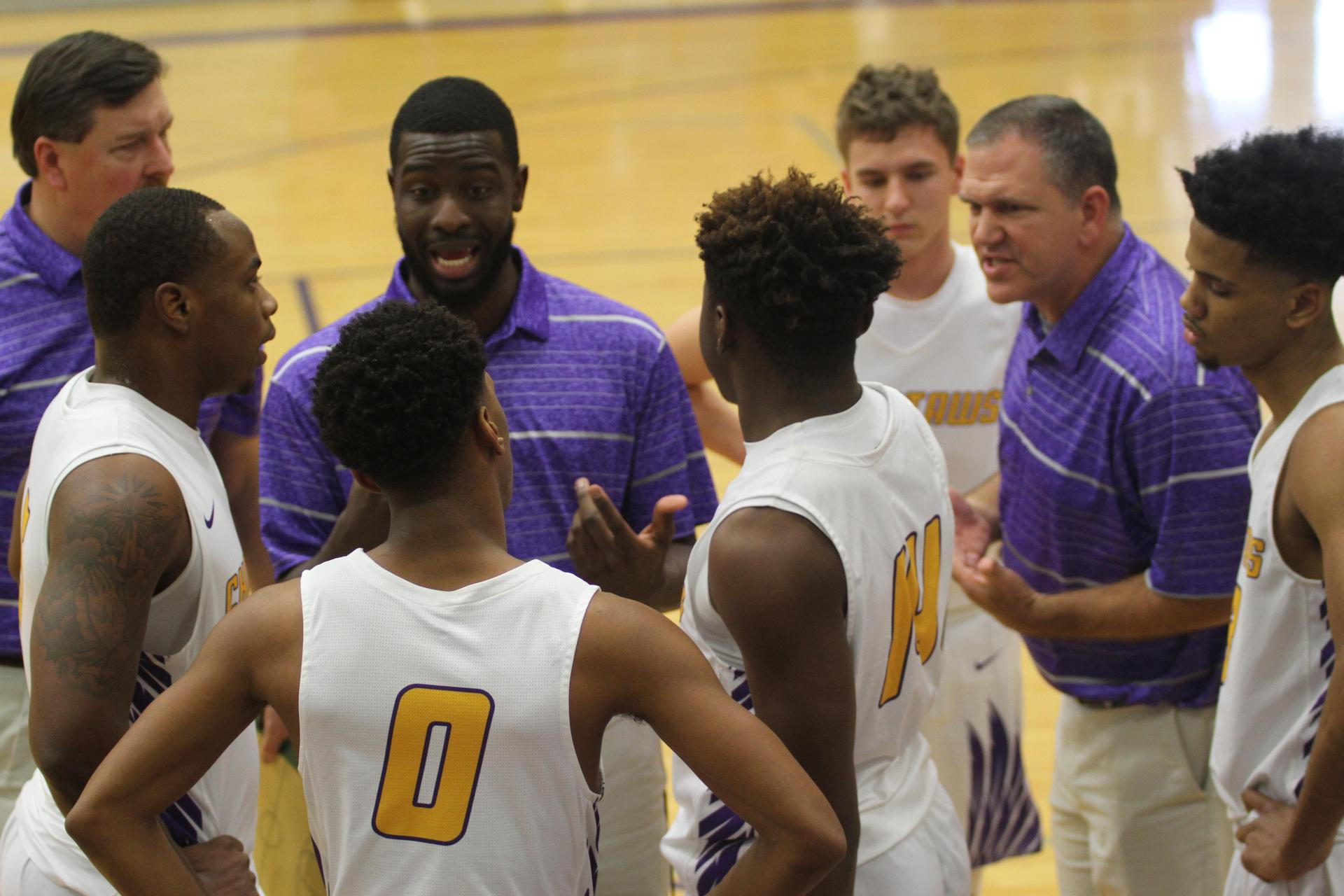 Coach Wallace and Coach Russell talk to players during a time out.
