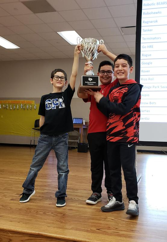 Three boys holding up large trophy