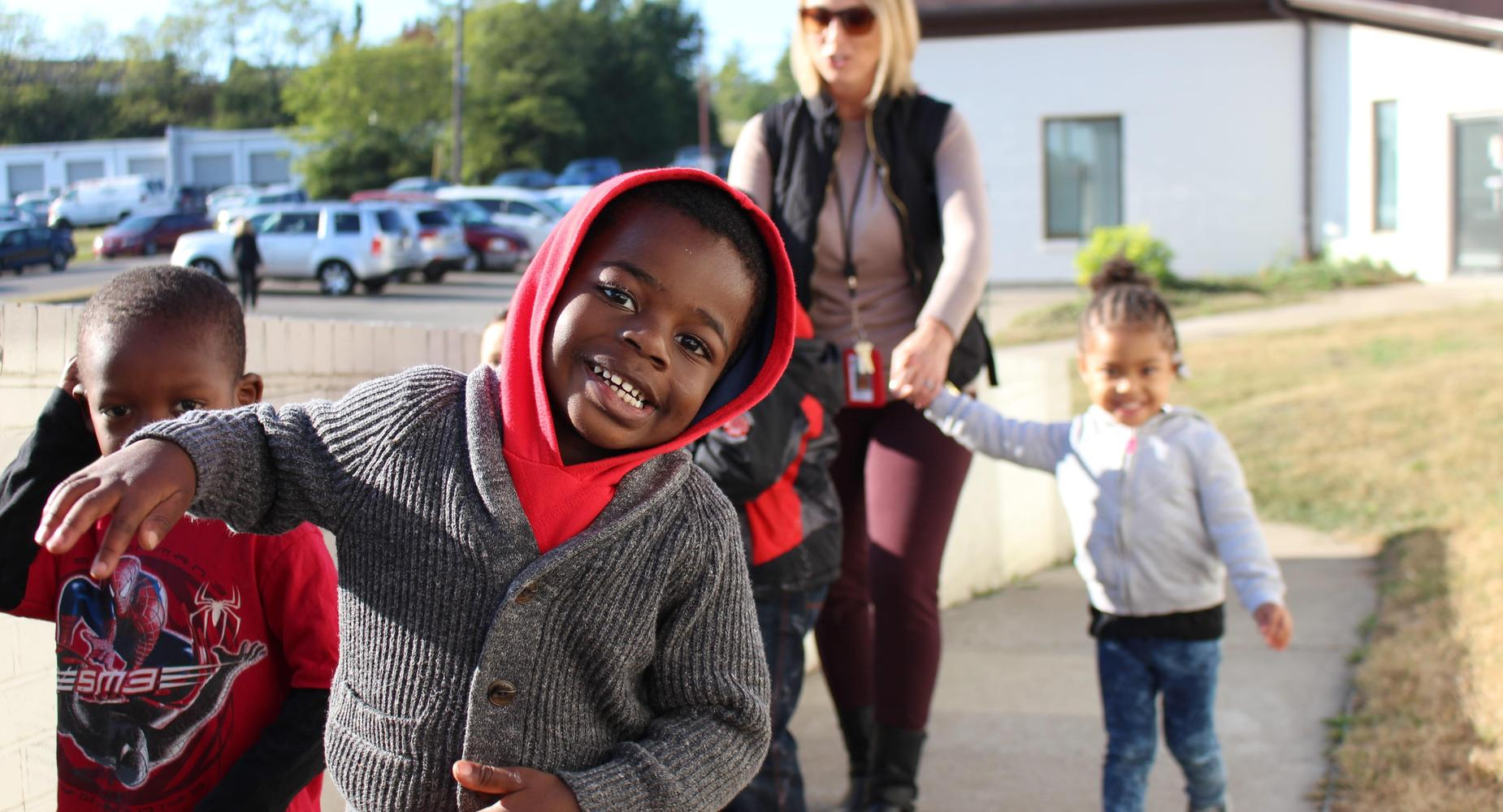 Young male Head Start student in a red hoodie smiling at the camera