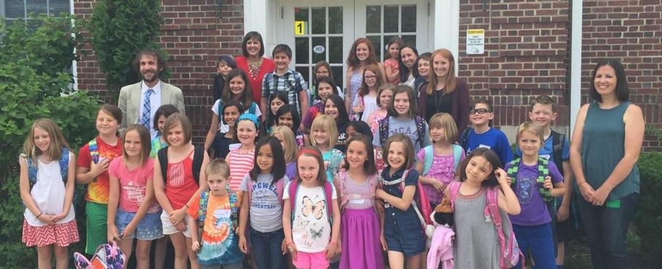 Participants in Locks of Love pose on the school front steps with Mr. Friedrich and teachers