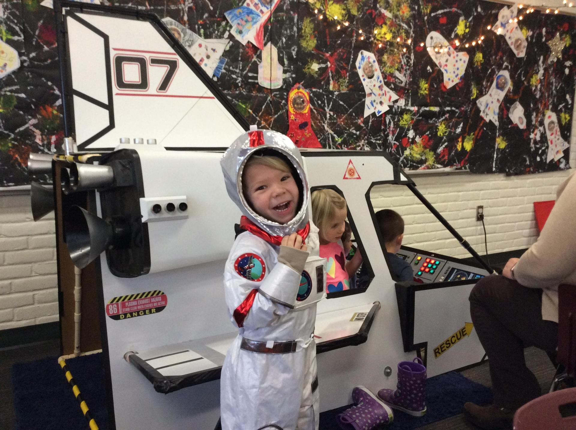 kid in spaceship suit by little rocket